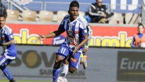 Fotbollsspelare springer med boll i solsken.