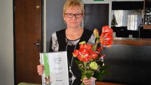 Seija Klemetti med diplom och blommor.