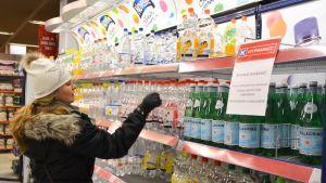 Kunden Pamela Massingberd-Lång inspekterar vattenflaskorna i Citymarket i Borgå.