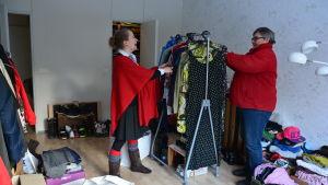 Två kvinnor går igenom kläder.