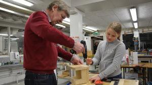 Kaj Fröberg och Alexandra Niemi bygger en fågelholk för en grå flugsnappare.