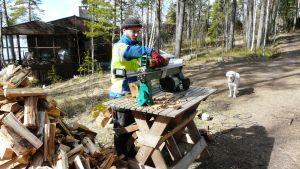 Byagårdskarlen Leif Still använder vedklyvaren i Pitkäpää medan hunden Cindy vill spela fotboll