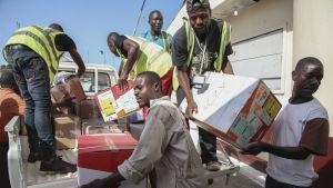 Liberiska män lastar av material som ska skydda mot Ebola.