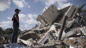 Man i Gaza tittar på ett hus som förstörts av en israelisk raket.