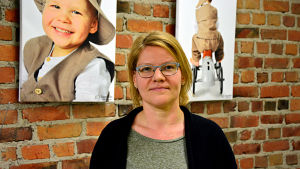 Virpi Hagström står framför en tegelvägg prydd av tavlor med fotografier av barn.