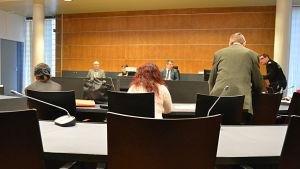 Rättsal, taget bakifrån från den åtalade med advokat och tolk. Domare och nämndemän i bakgrunden.