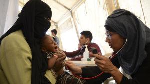 Läkare utan gränsers internationella ordförande Joanne Lui vårdar ett barn på besök i Jemen.