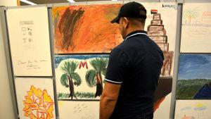 """""""Mohammed"""" vill vara anonym. Här står han framför den tavla han målat."""