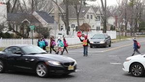 Jennifer Duteil står med en stoppskylt i handen och stoppar trafiken när barn går över gatan