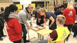 Tonåringar tittar på träbitar i en tävling där de ska känna igen träslag.