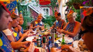 Ihmisiä pöydän ääressä rapujuhlissa