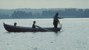 Mies (isoisä) kokemassa verkkoja soutuveneellä kahden lapsen kanssa.