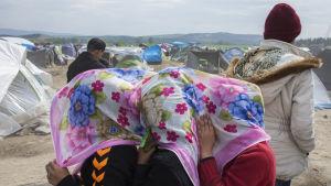 Tre flickor skyddar sina ansikten mot vinden i flyktinglägret Idomeni vid den grekiska gränsen till Makedonien.