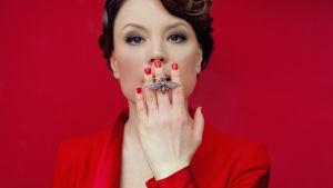 kvinna i klädd röd dräkt håller handen framför munnen. En fjärilsring pryder ett av fingrarna.