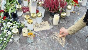 Kvinna ritar ett hjärta vid platsen där Jimi Karttunen blev misshandlad
