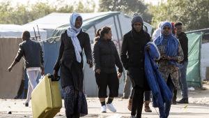 Människor i flyktinglägret i Calais bär på väskor 23.10.2016