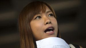 Självständighetsförespråkaren  Yau Wai-ching i Hongkong visar domarens beslut för journalister.