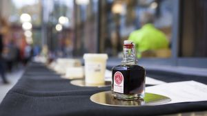 En flaska med ölvinäger. I bakgrunden kan man urskilja fler produkter på ett bord.