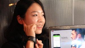 Sngl:s marknadsföringschef Saemi Kim visar hur man kan använda sitt öra som högtalare när man talar i telefon.