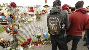 Personer står och tittar på blommor och ljus som har hämtats till olycksplatsen i Oakland.