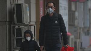 En pappa och ett barn går hand i hand genom utsläppsdimman i Peking den 20 december 2016.