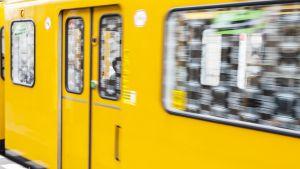 Ett gult tunnelbanetåg susar förbi i Berlin.