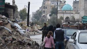 Människor går bland rasmassorna i det sönderbombade östra stadsdelarna av Aleppo.