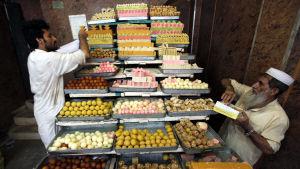 Försäljare i Pakistan radar upp sötsaker inför festhögtiden Eid al-Fitr.
