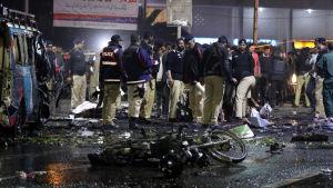 Poliser i Lahore står bland bråte bakom en motorcykel som användes i en självmordsattack.