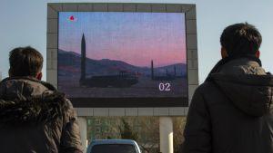 Nordkoreaner tittar på nyhetsinslag om missiltestet den 7.3. på en stor skärm på järnvägsstationen i Pyongyang.