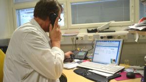 Läkare talar i telefon på mottagning.