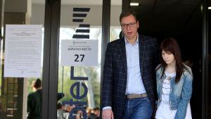 Aleksandar Vucic lämnar sin vallokal i Belgrad tillsammans med dottern Milica.