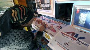 Vid en tidningskiosk i Belgrad bläddrar en kvinna bland tidningar som alla gör reklam för Aleksandar Vucic på sina paradsidor.