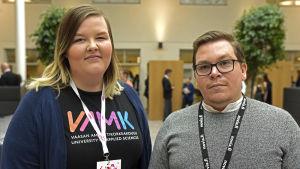 Henna Tihinen har en svart t-skjorta med Vasa yrkeshögskolas logo på och ett guide-pass runt halsen. Anton Malinen-Lind har en grå tröja och ett likadant pass runt halsen.
