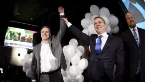 Partiordförande Petteri Orpo håller upp Jan Vapaavuoris arm i luften i en segergest med ballonger i bakgrunden.