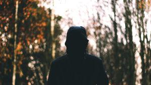 En man med dolt ansikte står i en skog.