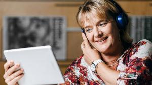 Camilla Kivivuori pitää kiinni tablettilaitteesta ja katsoo siihen kuulokkeet korvilla