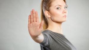 Kvinna håller upp en hand för att signalera stopp.