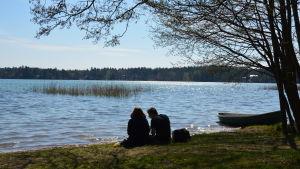 En kvinna och en man sitter vid strandbrynet en solig dag. Havet glittrar och man ser dem i motljus.