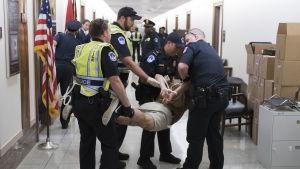 En hiv-positiv man som deltar i demonstrationen bärs bort av polisen.