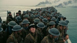 En soldat står på en överfylld pir tittar upp mot himlen.