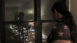 Yksi Angulon veljeksistä katselee illalla kotona ulos ikkunasta. Kuva dokumenttielokuvasta The Wolfpack.
