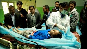 Läkare vårdar en liten pojke som skadades i attacken.