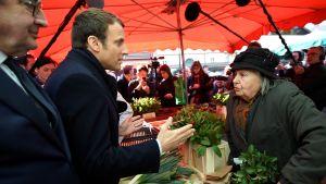 Emmanuel Macron diskuterar med en torghandlare i Poitiers, i centrala Frankrike, på lördagen 29.4.2017