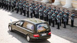 Surusaatto, musta ruumisauto sotilasrivistön edessä