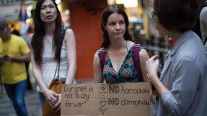 """En person i Hong Kong, Kina, håller upp en skylt med texten """"Vår sorg är inte ett rop för krig"""" samt """"Nej till homofobi"""" och """"Nej till islamofobi""""."""
