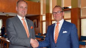 Raseborgs stadsdirektör Tom Simola och Hangös stadsdirektör Denis Strandell skakar hand.