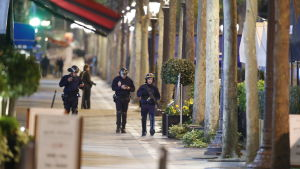 Poliser vandrar längs i övrigt folktomma Champs-Elysees i Paris, i kölvattnet efter en attack där en polis misste livet.