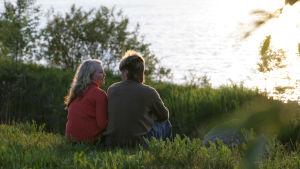 En kvinna och en man sitter i gräset och blickar ut över sjön i ljus som påminner om solnedgång.