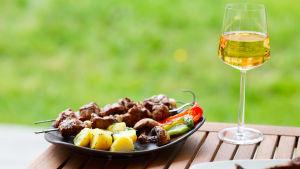 En portion med grillmat står på ett utebord i trä. Ett glas med vitt vin står bredvid.